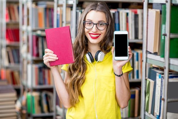 Jeune étudiant souriant tenant un livre et un téléphone intelligent avec un écran vide debout à la bibliothèque. concept d'applications mobiles