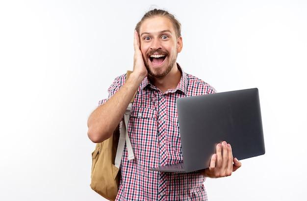 Jeune étudiant surpris portant un sac à dos tenant un ordinateur portable mettant la main sur la joue