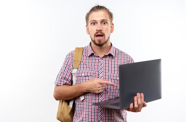 Jeune étudiant surpris portant un sac à dos tenant et pointant sur un ordinateur portable isolé sur un mur blanc