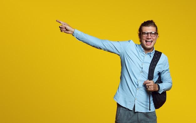 Jeune étudiant tenant un sac à dos et pointant vers l'extérieur sur le mur jaune
