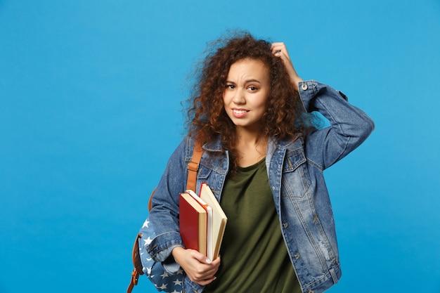 Jeune étudiant triste en vêtements en jean et sac à dos tient des livres isolés sur un mur bleu