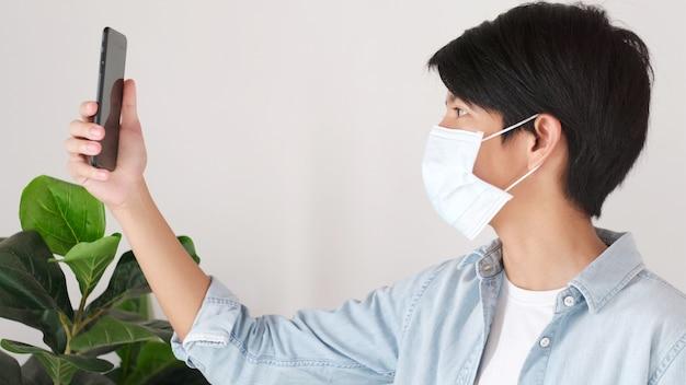 Jeune étudiant universitaire asiatique tenant un téléphone portable et passant un appel vidéo tout en portant un masque de protection sur le campus, distanciation sociale, covid 19