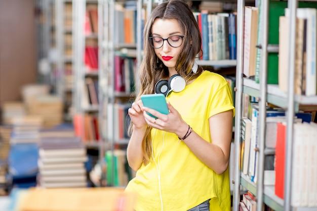 Jeune étudiant utilisant un téléphone intelligent à la bibliothèque