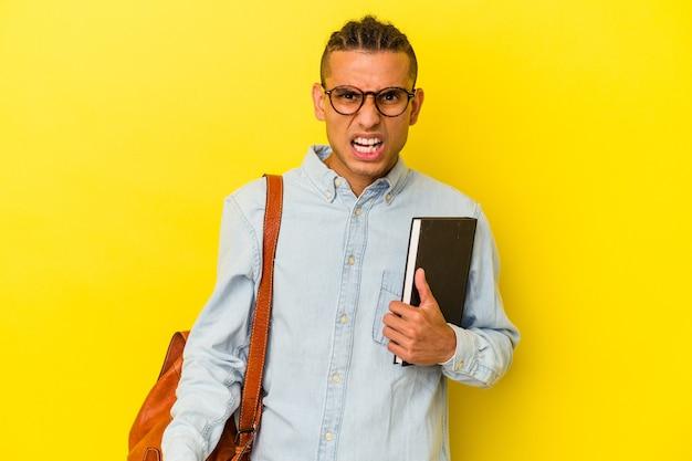Jeune étudiant vénézuélien isolé sur fond jaune criant très en colère et agressif.