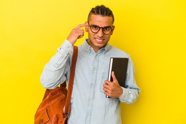 Jeune étudiant vénézuélien isolé sur fond jaune montrant un geste de déception avec l'index.