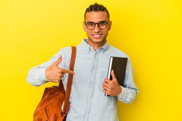 Jeune étudiant vénézuélien isolé sur fond jaune personne pointant à la main vers un espace de copie de chemise, fier et confiant