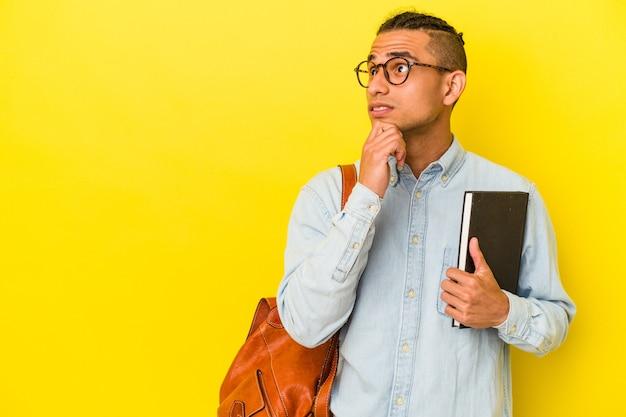 Jeune étudiant vénézuélien isolé sur fond jaune regardant de côté avec une expression douteuse et sceptique.