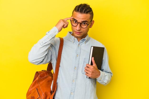 Jeune étudiant vénézuélien isolé sur un mur jaune pointant le temple avec le doigt, pensant, concentré sur une tâche.