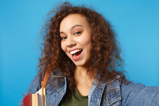 Jeune étudiant en vêtements en jean et sac à dos tient des livres et fait une photo de selfie isolée sur un mur bleu