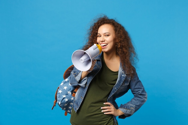 Jeune étudiante adolescente afro-américaine dans des vêtements en denim, sac à dos tenir un mégaphone isolé sur un mur bleu