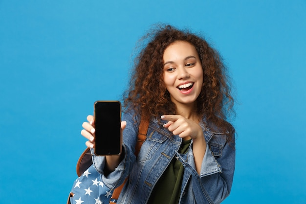 Jeune étudiante adolescente afro-américaine dans des vêtements en denim, sac à dos tenir le téléphone isolé sur le mur bleu