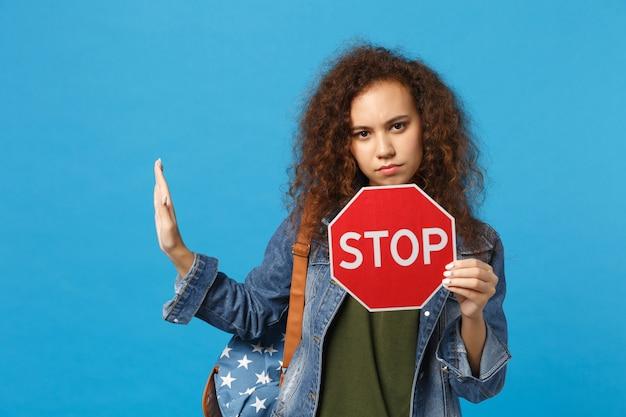 Jeune étudiante adolescente afro-américaine en vêtements en jean, arrêt de prise de sac à dos isolé sur mur bleu