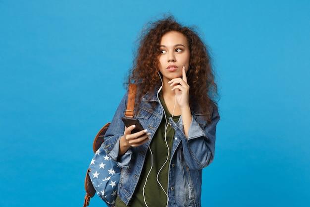 Jeune étudiante adolescente afro-américaine en vêtements en jean, casque d'écoute à dos isolé sur mur bleu