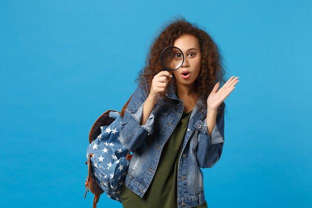 Jeune étudiante adolescente afro-américaine en vêtements en jean, horloge de maintien de sac à dos isolée sur mur bleu