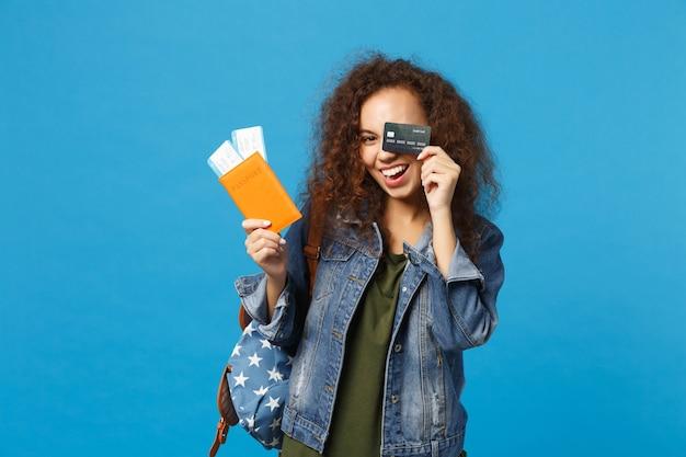 Jeune étudiante adolescente afro-américaine en vêtements en jean, passe de maintien de sac à dos isolé sur mur bleu
