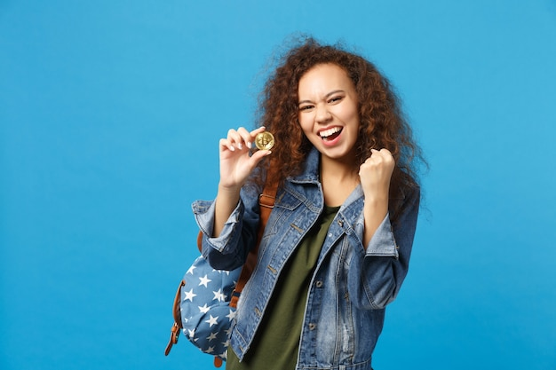 Jeune étudiante adolescente afro-américaine en vêtements en jean, sac à dos tenir bitcoin isolé sur mur bleu