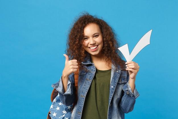 Jeune étudiante adolescente afro-américaine en vêtements en jean, sac à dos tenir chèque isolé sur mur bleu