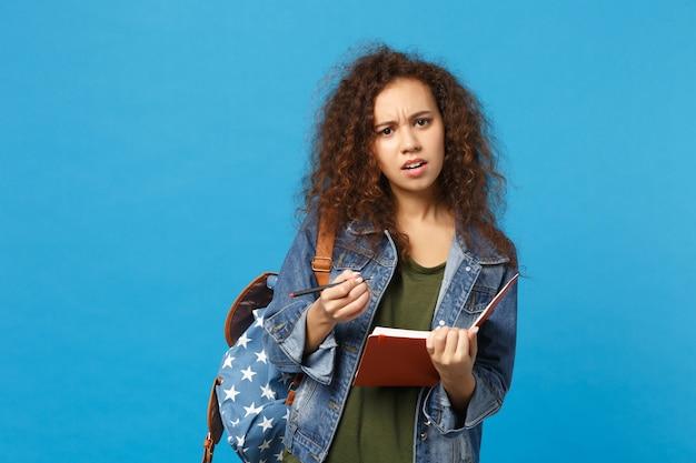 Jeune étudiante adolescente afro-américaine en vêtements en jean, sac à dos tenir des livres isolés sur le mur bleu