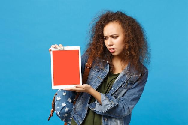 Jeune étudiante adolescente afro-américaine en vêtements en jean, sac à dos tenir pad pc isolé sur mur bleu