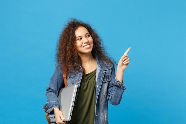 Jeune étudiante adolescente afro-américaine en vêtements en jean, sac à dos tenir pc isolé sur mur bleu