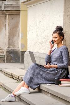 Jeune étudiante adulte parlant par smartphone assis sur les escaliers avec ordinateur portable près du bâtiment de l'université