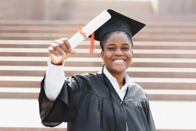 Jeune étudiante afro-américaine avec diplôme pose à l'extérieur.