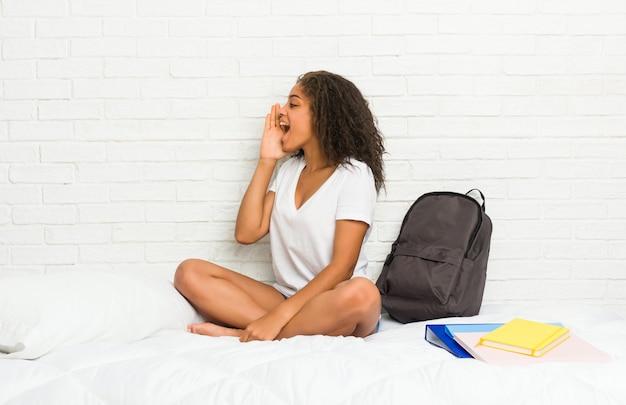 Jeune étudiante afro-américaine femme sur le lit en criant et en tenant la paume près de la bouche ouverte.