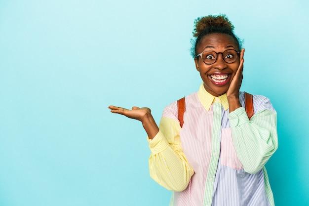 Jeune étudiante afro-américaine sur fond isolé détient un espace de copie sur une paume, gardez la main sur la joue. émerveillé et ravi.