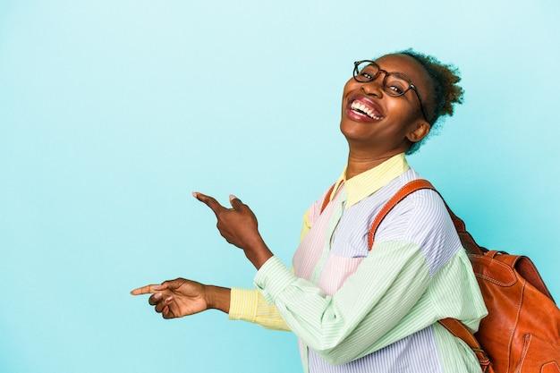 Jeune étudiante afro-américaine sur fond isolé excité pointant avec les index loin.