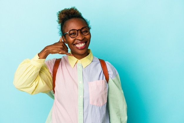 Jeune étudiante afro-américaine sur fond isolé montrant un geste d'appel de téléphone portable avec les doigts.