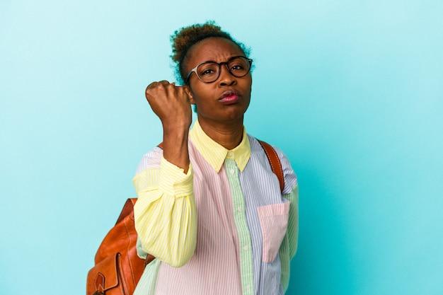 Jeune étudiante afro-américaine sur fond isolé montrant le poing à la caméra, expression faciale agressive.