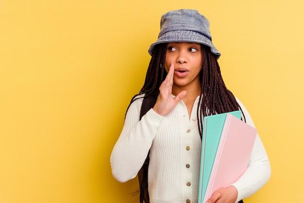 Jeune étudiante afro-américaine isolée sur le mur jaune dit une nouvelle secrète de freinage à chaud et à la recherche de côté