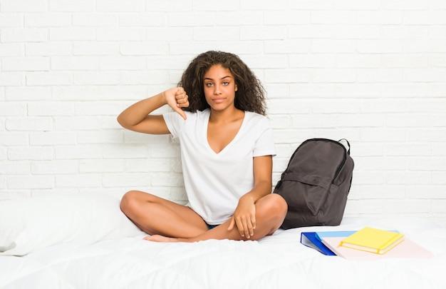 Jeune étudiante afro-américaine sur le lit, montrant un geste d'aversion, les pouces vers le bas. concept de désaccord.