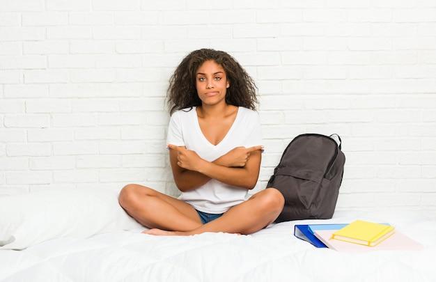 Une jeune étudiante afro-américaine sur le lit pointe sur le côté, essaie de choisir entre deux options.
