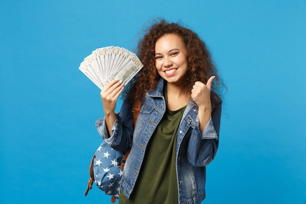 Jeune étudiante afro-américaine en vêtements en denim, sac à dos contenant de l'argent en espèces isolé sur le mur bleu