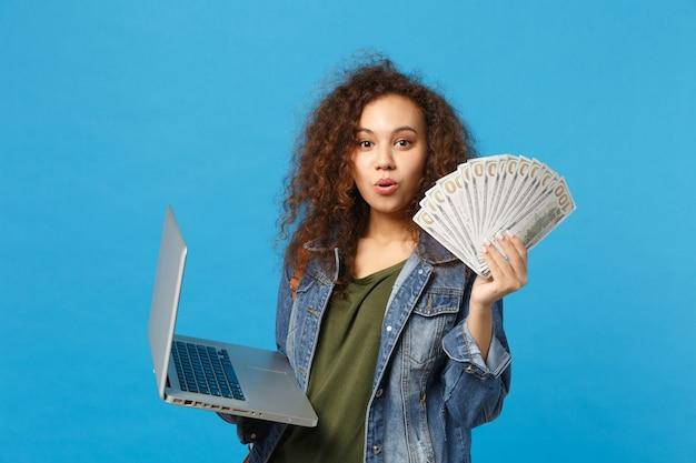 Jeune étudiante afro-américaine en vêtements en denim, sac à dos, ordinateur portable, fan d'argent liquide isolé sur mur bleu