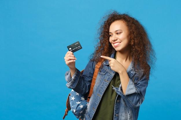 Jeune étudiante afro-américaine en vêtements en jean, sac à dos avec carte de crédit isolée sur mur bleu