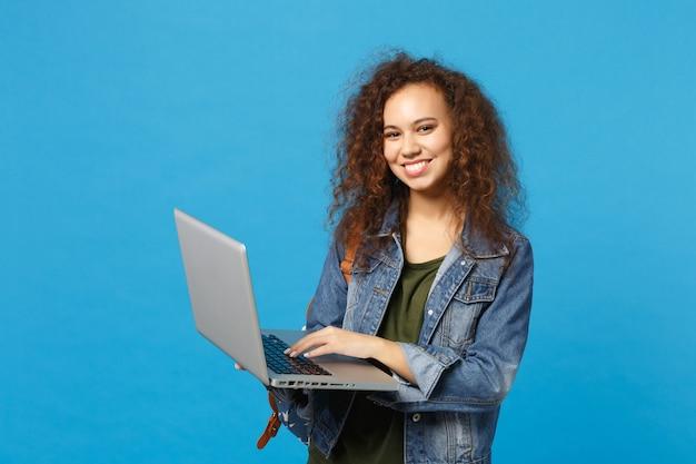 Jeune étudiante afro-américaine en vêtements en jean, travail de sac à dos sur pc isolé sur mur bleu