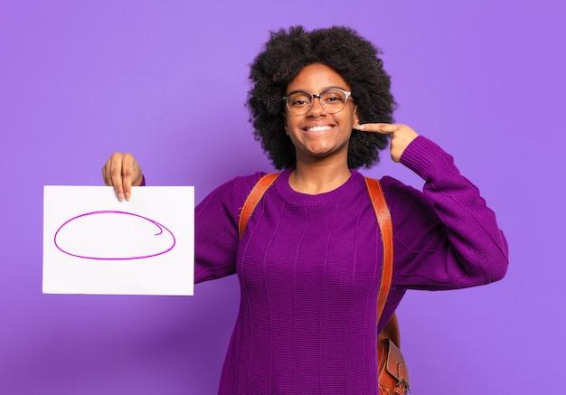 Jeune étudiante afro souriante pointant avec confiance vers son propre large sourire, attitude positive, détendue et satisfaite