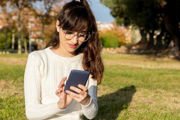 Jeune étudiante à l'aide de sa calculatrice dans le parc
