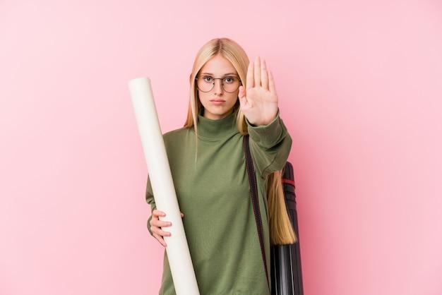 Jeune étudiante en architecture blonde debout avec la main tendue montrant le panneau d'arrêt, vous empêchant.