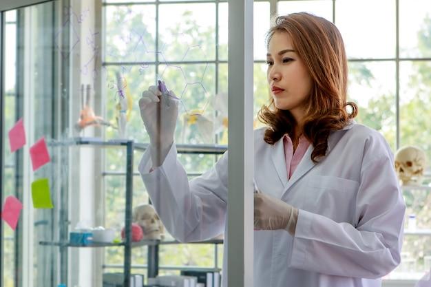 Jeune étudiante asiatique en chimie écrivant des formules sur un mur de verre tout en menant des recherches avec un collègue dans un laboratoire universitaire.