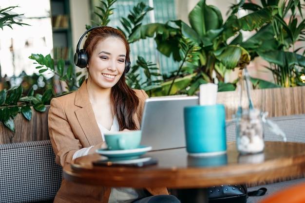 Jeune étudiante asiatique souriante dans les écouteurs communique par tablette apprendre une langue étrangère au café