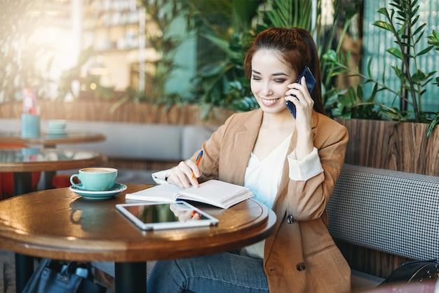 Jeune étudiante asiatique souriante à faire ses devoirs dans un ordinateur portable avec tablette sur table à l'aide de téléphone mobile au café