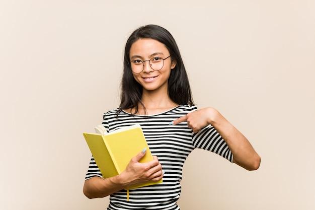 Jeune étudiante asiatique tenant un livre personne pointant à la main vers un espace vide de chemise, fier et confiant