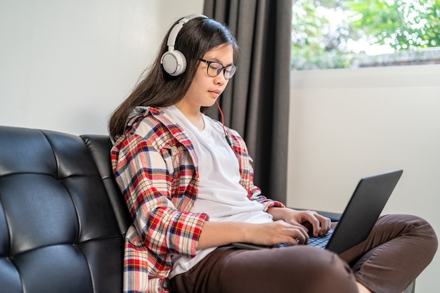 Une jeune étudiante asiatique travaillant et étudiant à domicile pendant le verrouillage de la ville en raison de la propagation du virus corona