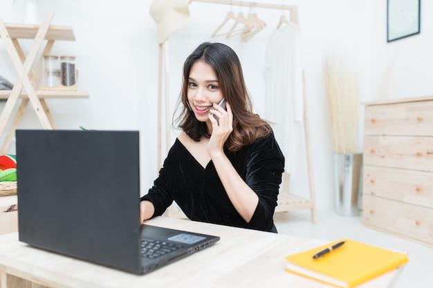 Jeune étudiante asiatique travaillant avec un ordinateur portable et parlant à un téléphone portable tout en apprenant en ligne
