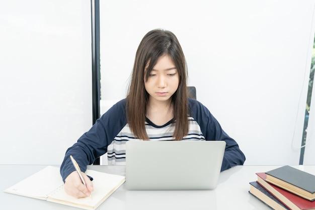 Jeune étudiante assise dans le salon et apprendre en ligne