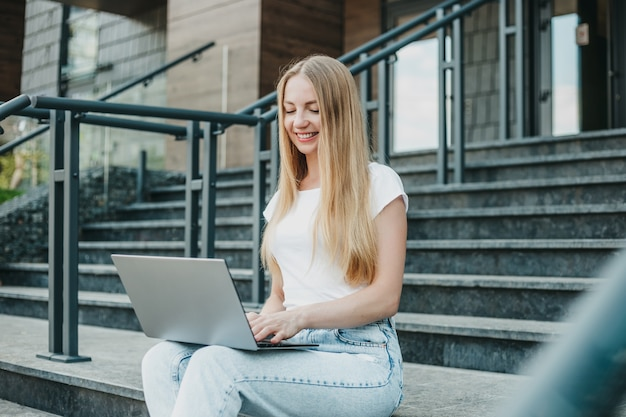 Jeune étudiante assise avec un ordinateur portable dans les escaliers près de l'université souriant et étudiant