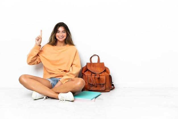 Jeune étudiante assise sur le sol avec un ordinateur portable isolé sur fond blanc pointant vers une excellente idée